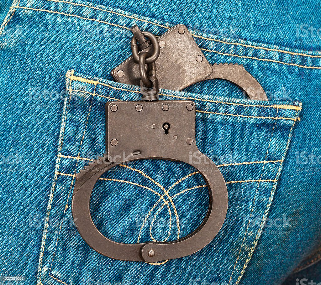 Police steel handcuffs in back jeans pocket stock photo