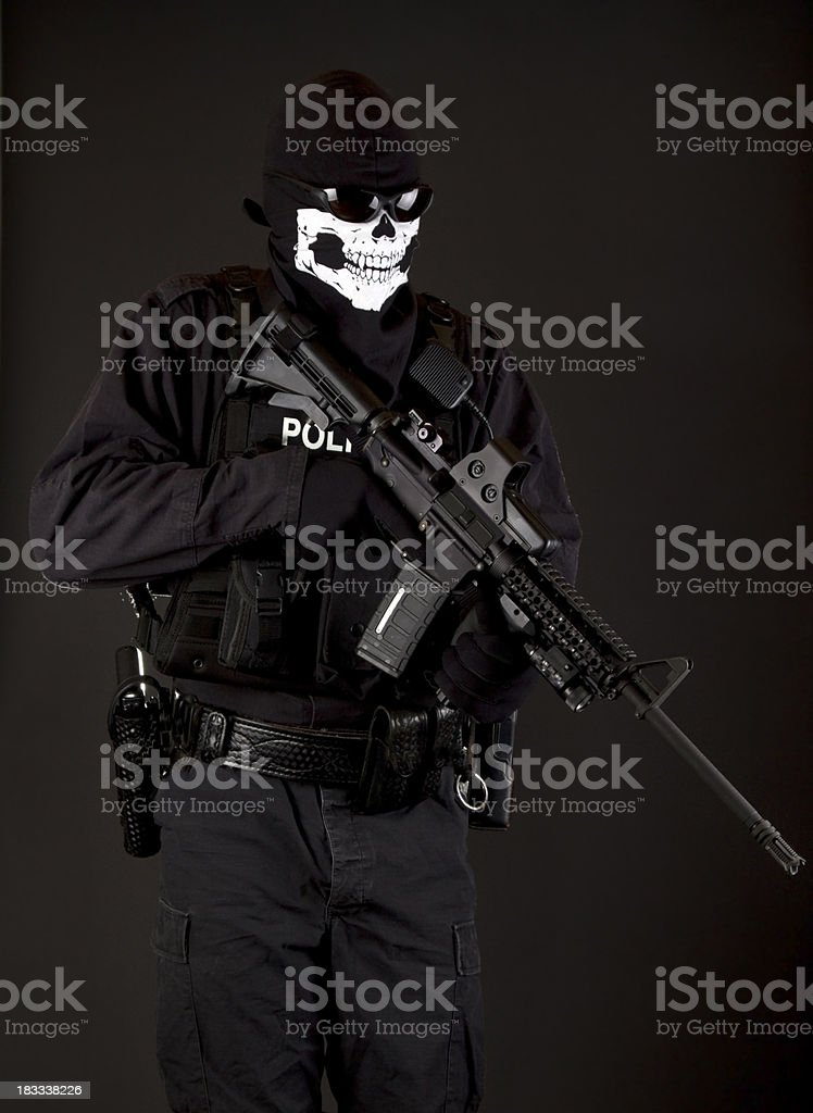 Police SWAT Officer wearing Ghost Skeleton Mask with Rifle stock photo