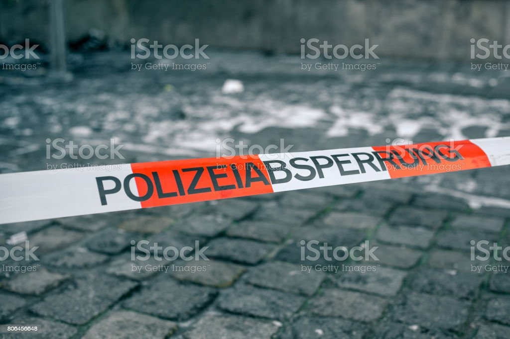 Police tape in Germany at the crime scene with the inscription in German police cordon. Crime Scene. stock photo