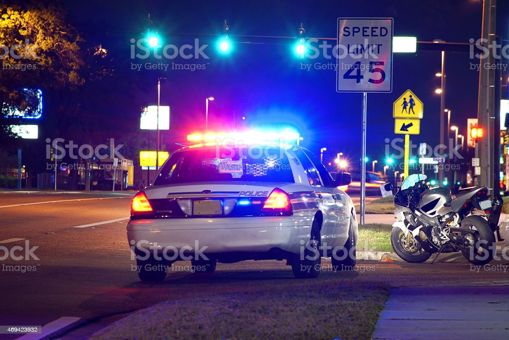 Police traffic stop at night with motorcycle pulled over stock photo