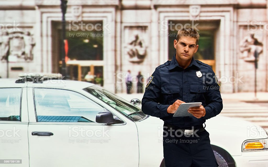 Police using tablet outdoors stock photo