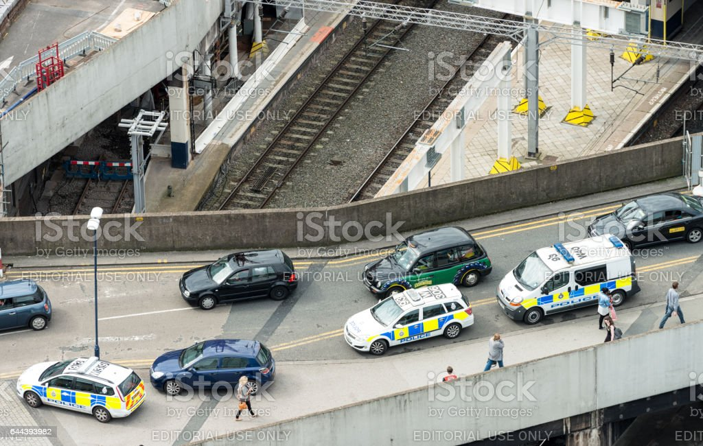 Pedestrians passing police vehicles surrounding a stopped car on a...