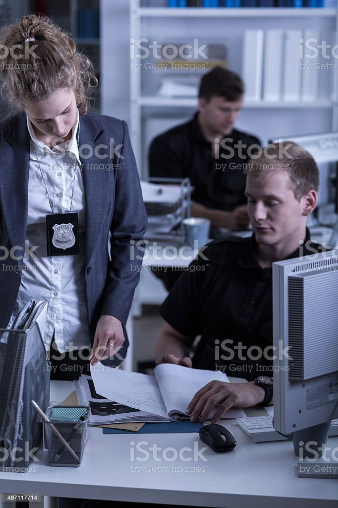 Police woman reviewing files stock photo