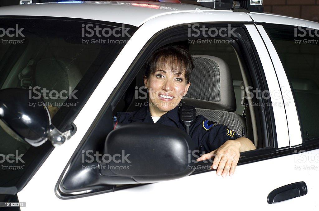 Police woman smiling inside patrol car at night stock photo