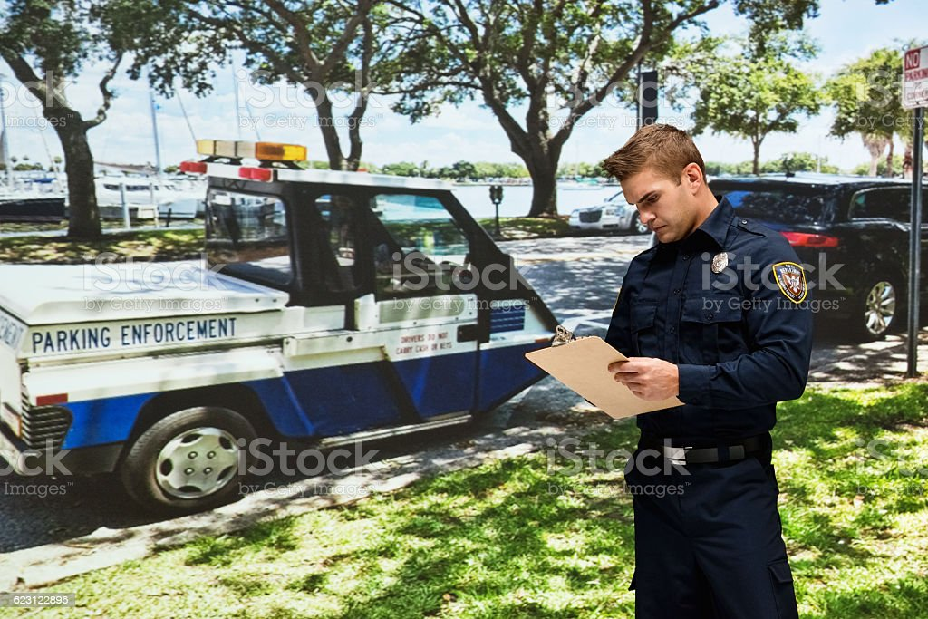 Police working with clipboard outdoors stock photo