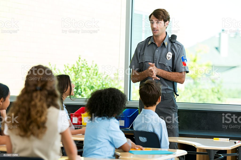 Policeman addresses a classroom of private school students stock photo