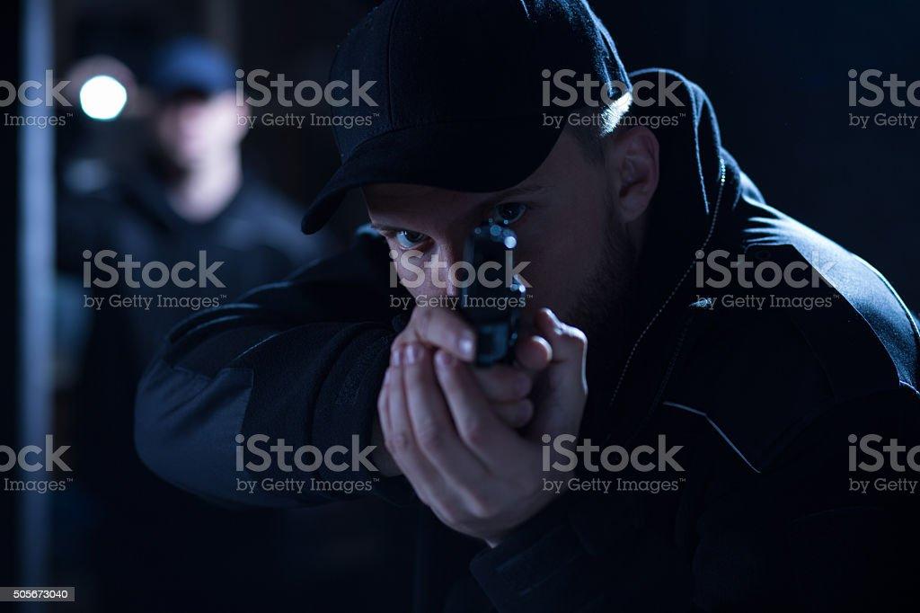 Policeman aiming gun during intervention stock photo