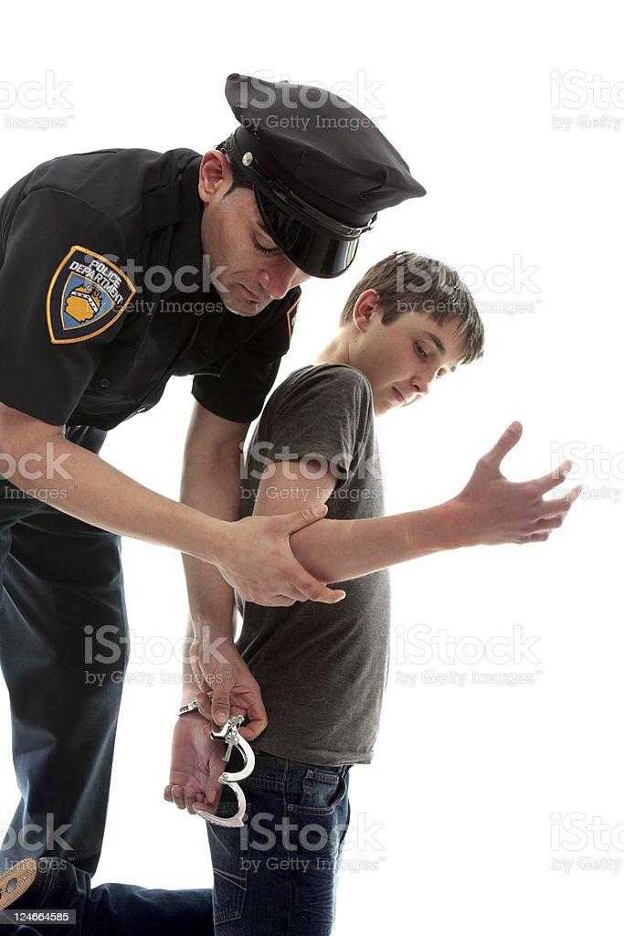 Policeman arresting teen criminal stock photo
