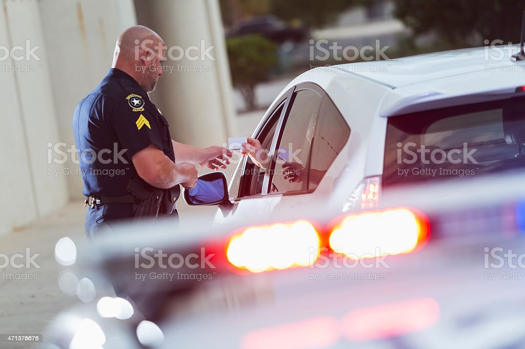 Policeman asking a driver for identification stock photo