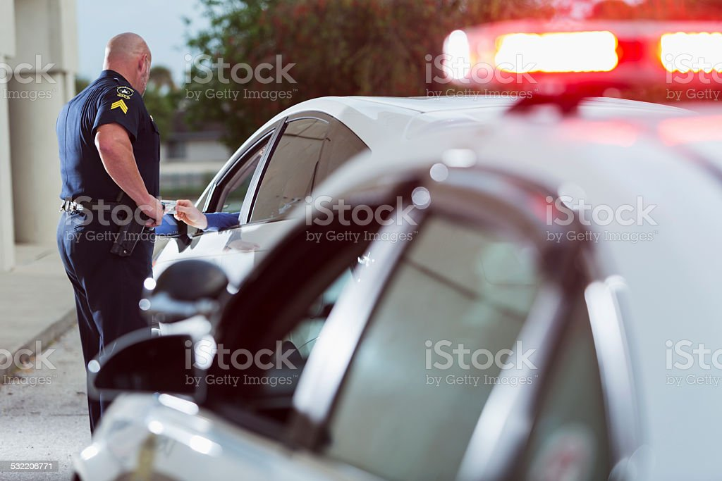 Policeman asking driver for identification stock photo