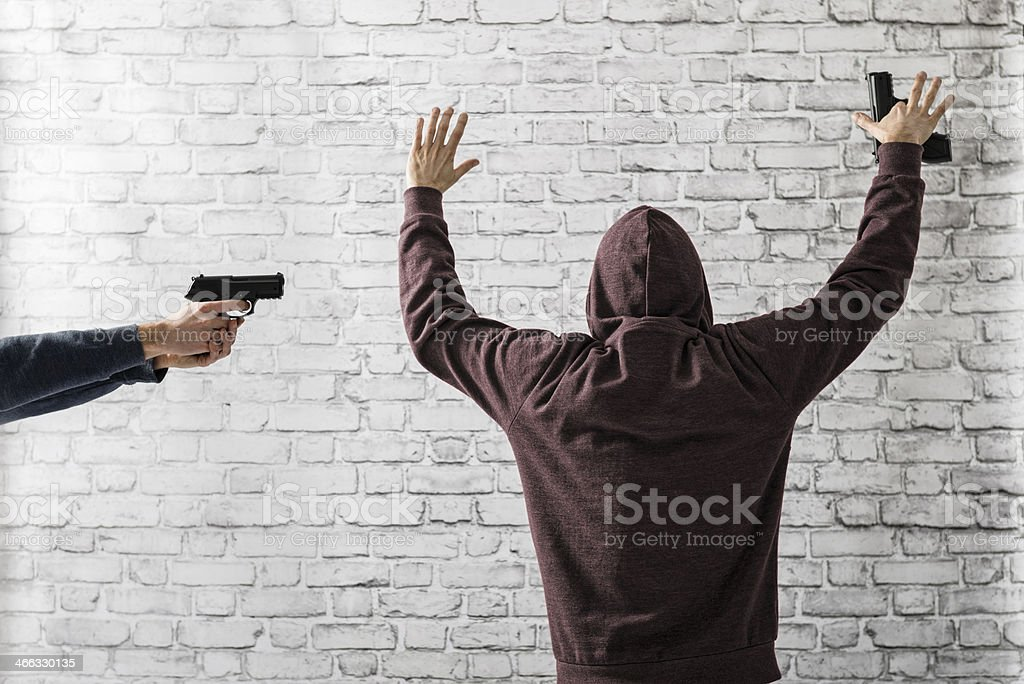Policeman, detective during arresting suspected criminal with gun stock photo