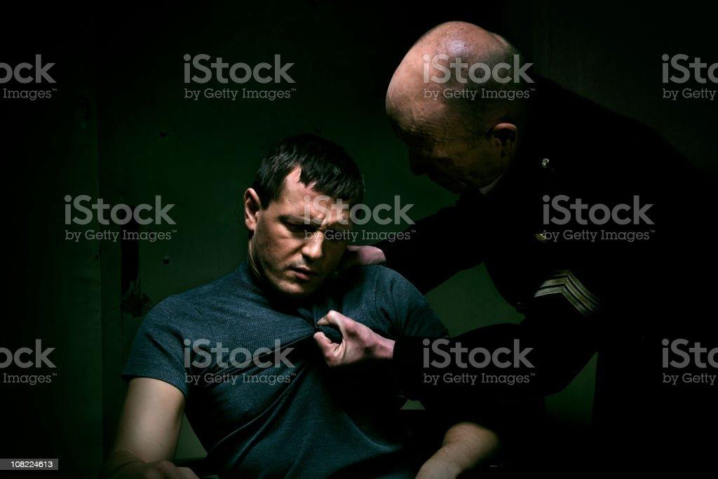 Policeman grabbing man's tshirt during interrogation stock photo