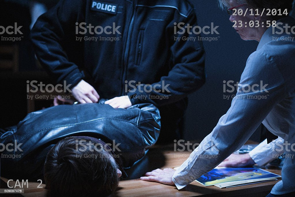 Policeman handcuffing a suspect stock photo