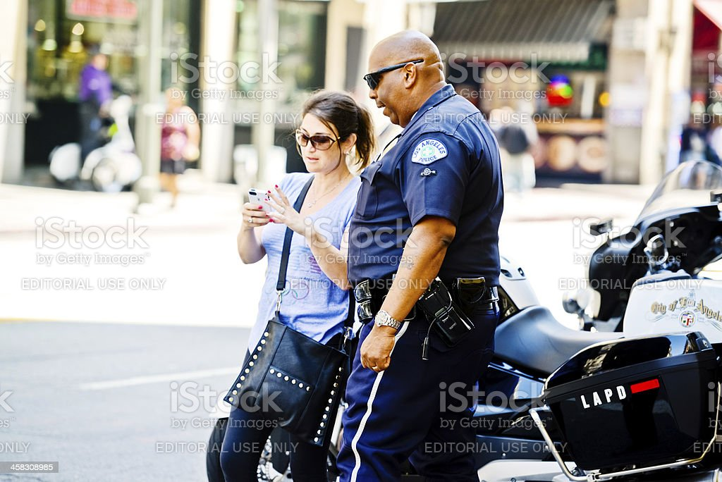 Policeman helping woman on Los Angeles street royalty-free stock photo