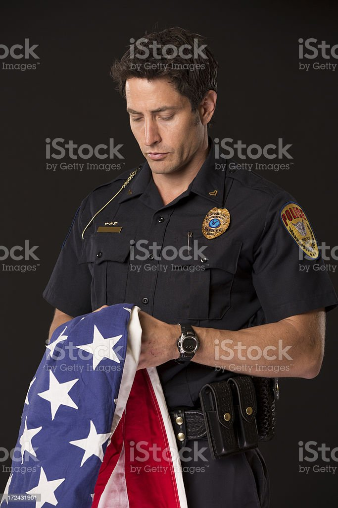 Policeman holding an American Flag royalty-free stock photo