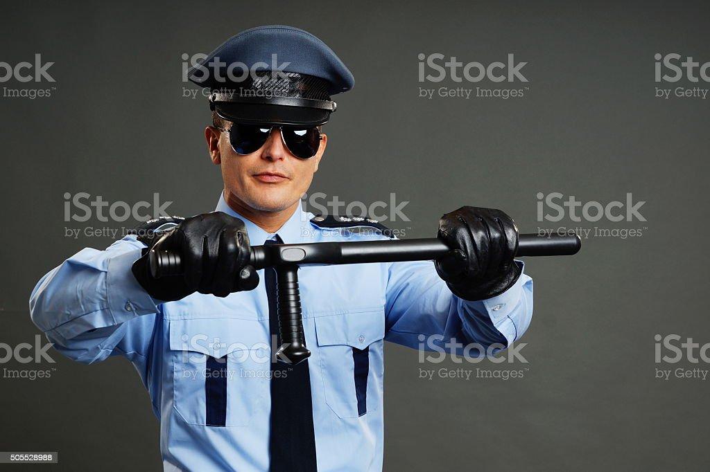 Policeman holds nightstick stock photo