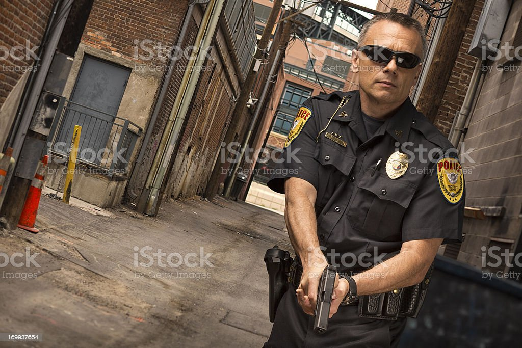 Policeman in Ally looking for suspect stock photo