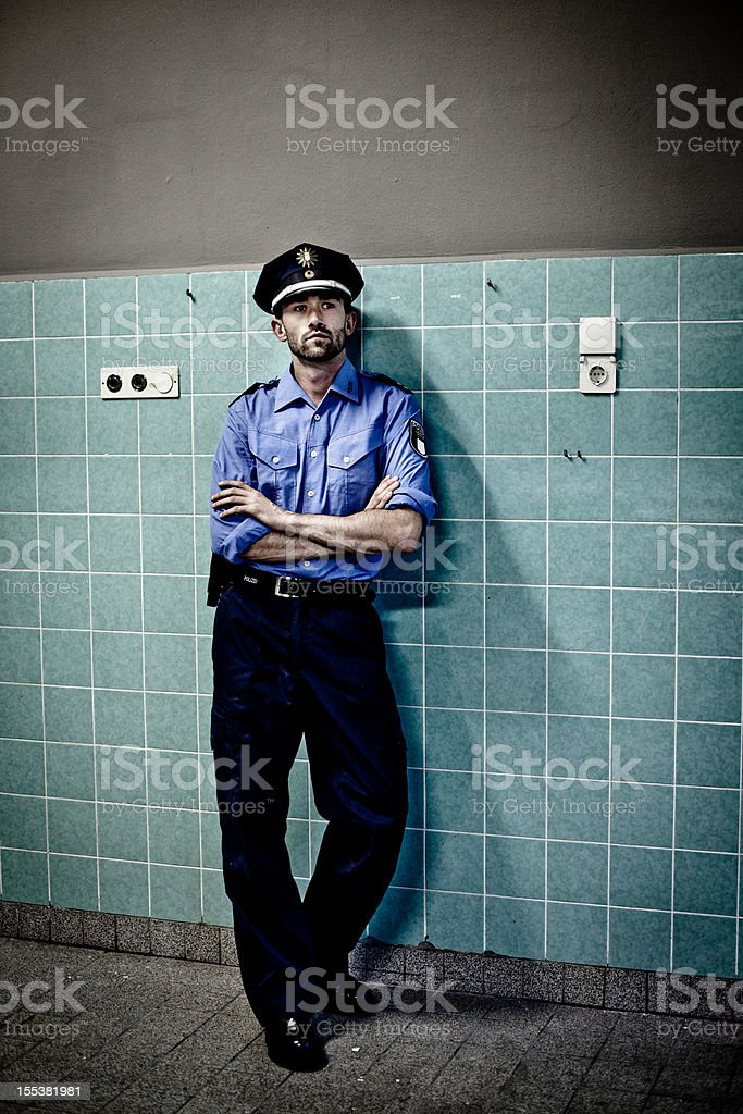 policeman in blue uniform leans against a tiled wall royalty-free stock photo