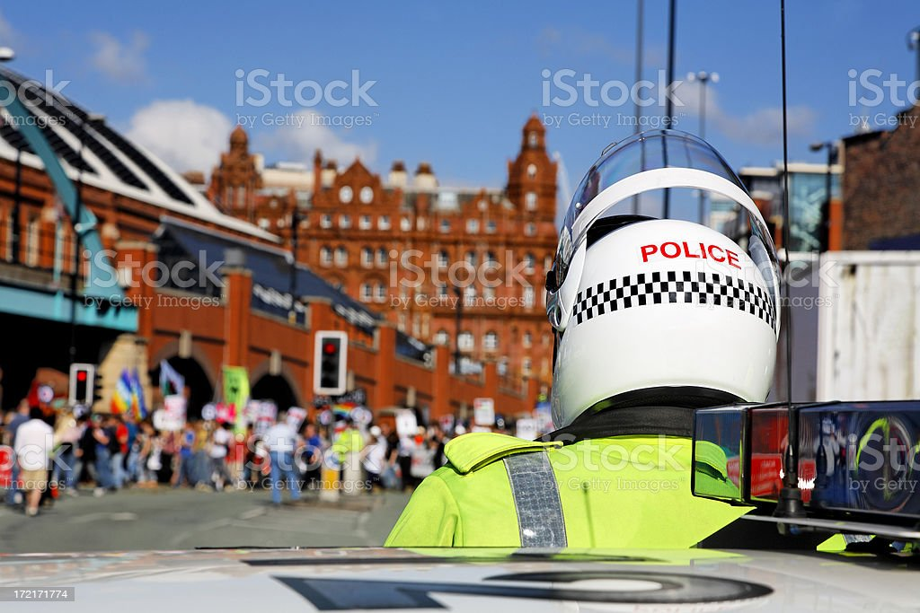 Policeman in Motorcycle Helmet Watches City Centre March. More below..... stock photo