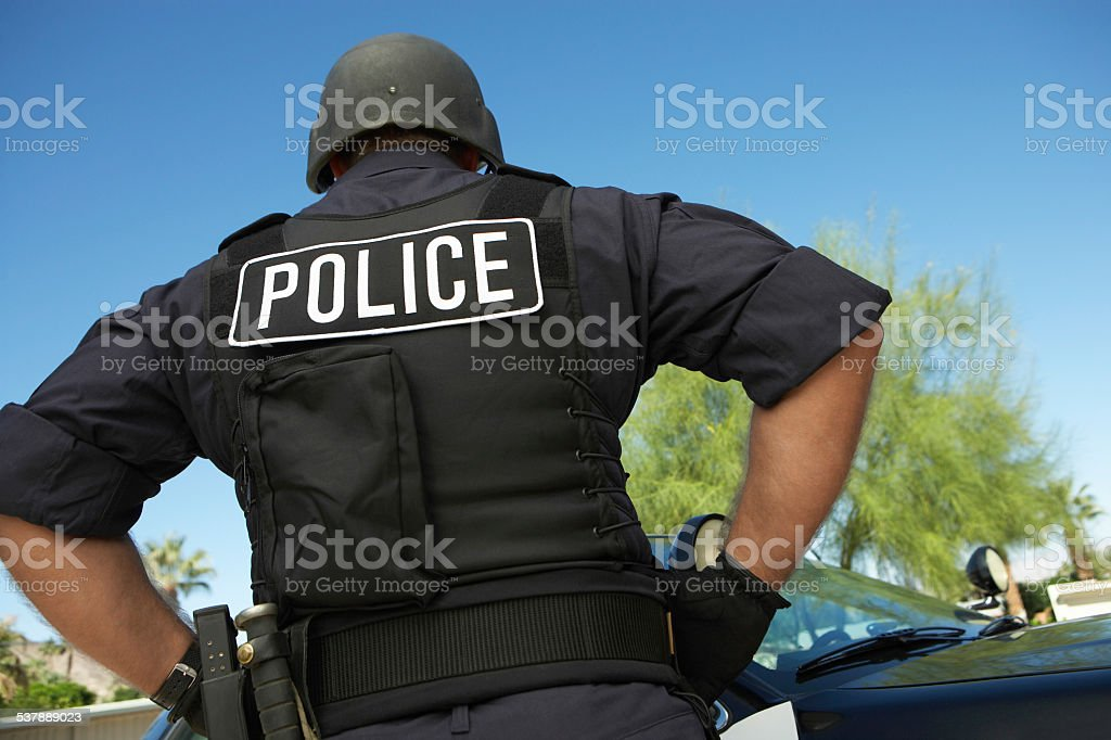 Policeman In Uniform Standing Against Car stock photo