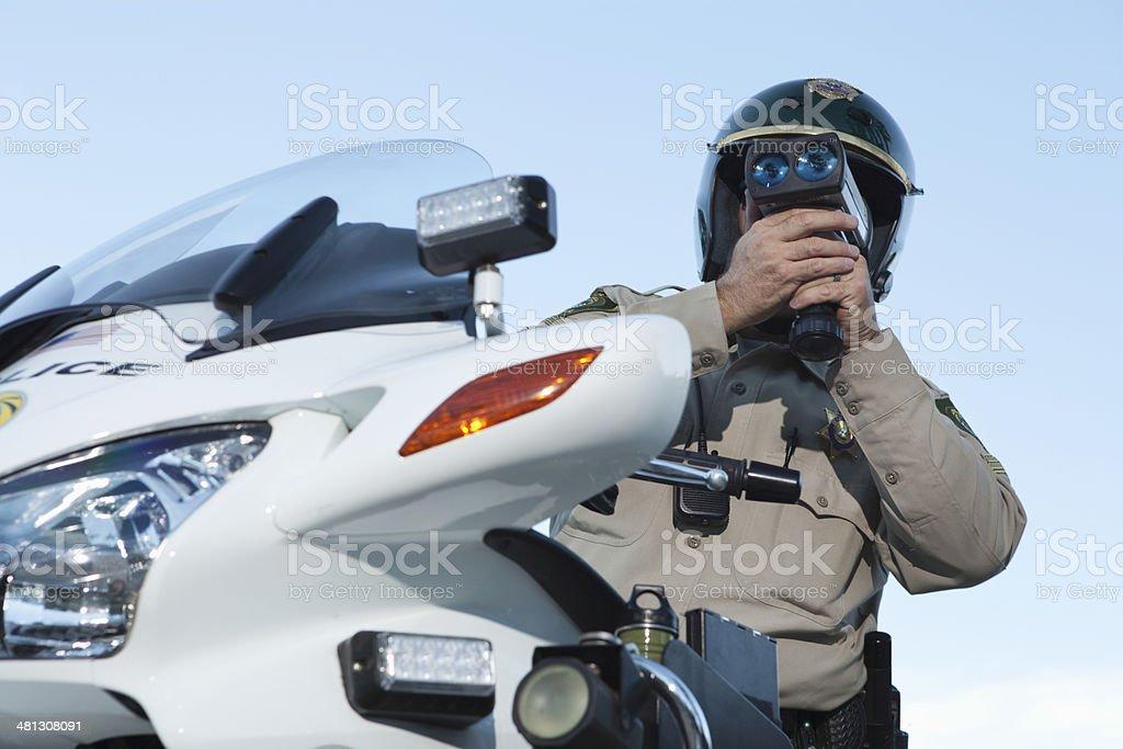 Policeman Monitoring Speed Through Radar Against Sky stock photo