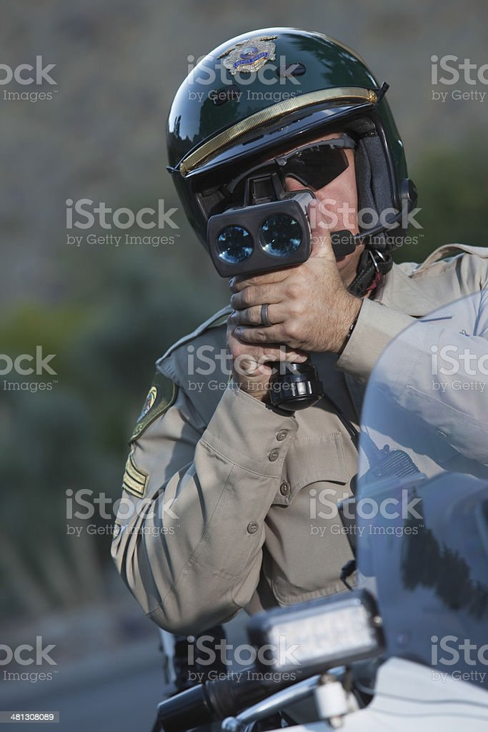 Policeman Monitoring Speed Through Radar While Sitting On Bike stock photo