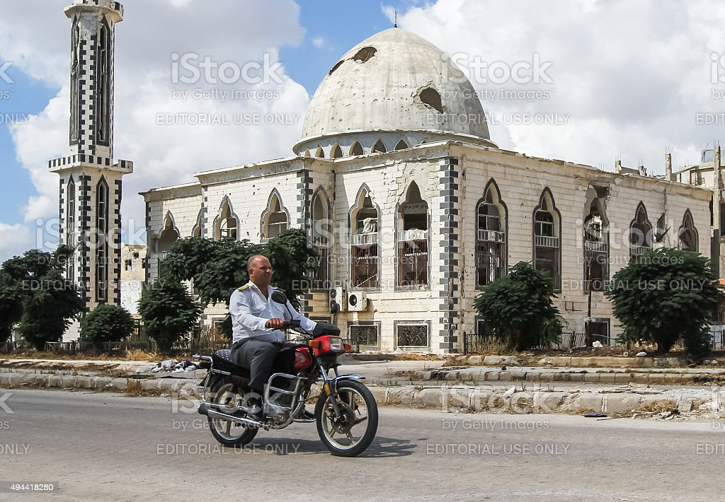Policeman passes near the damaged mosque in Homs stock photo