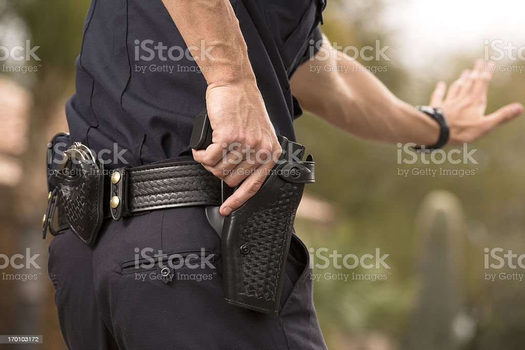 Policeman preparing to draw his gun stock photo