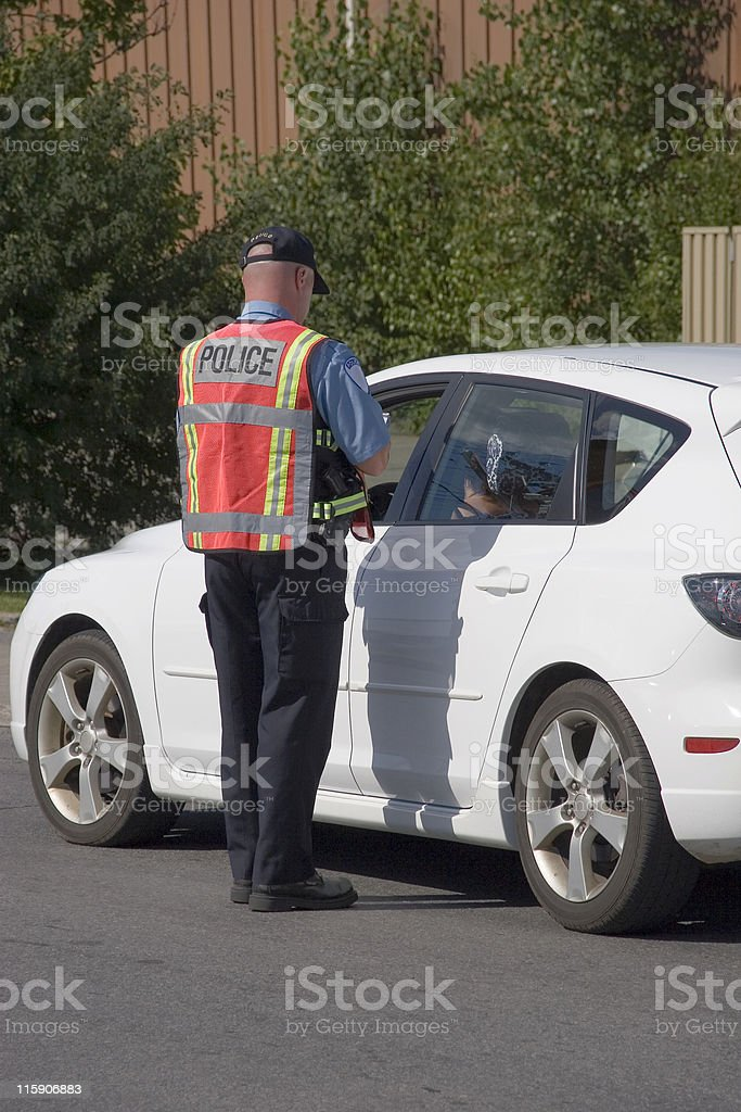 A policeman pulling over a white car for speeding stock photo