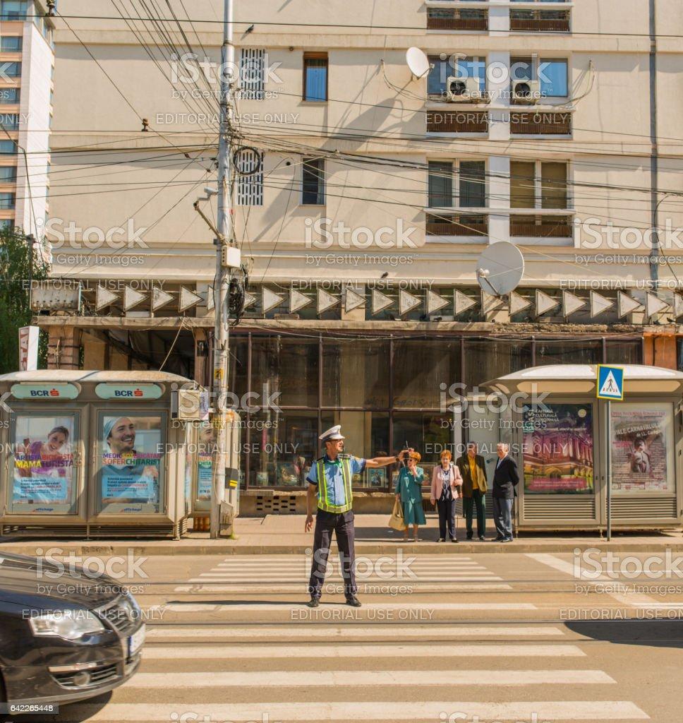 Policeman regulates local traffic on the road. Iasi, Romania. stock photo