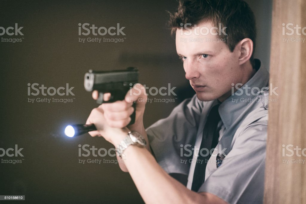 Policeman Searching a Dark Room stock photo
