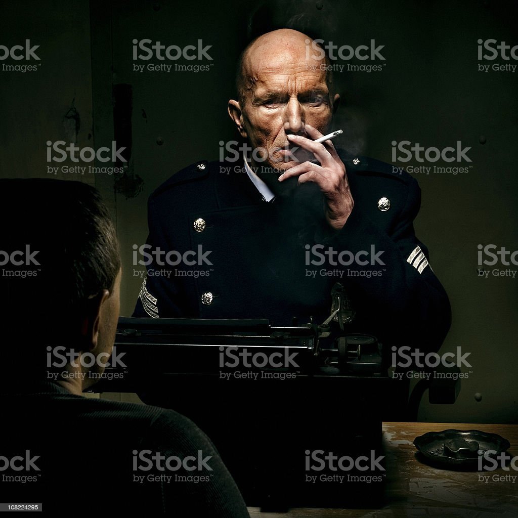Policeman SItting in Interrogation Room and Smoking royalty-free stock photo