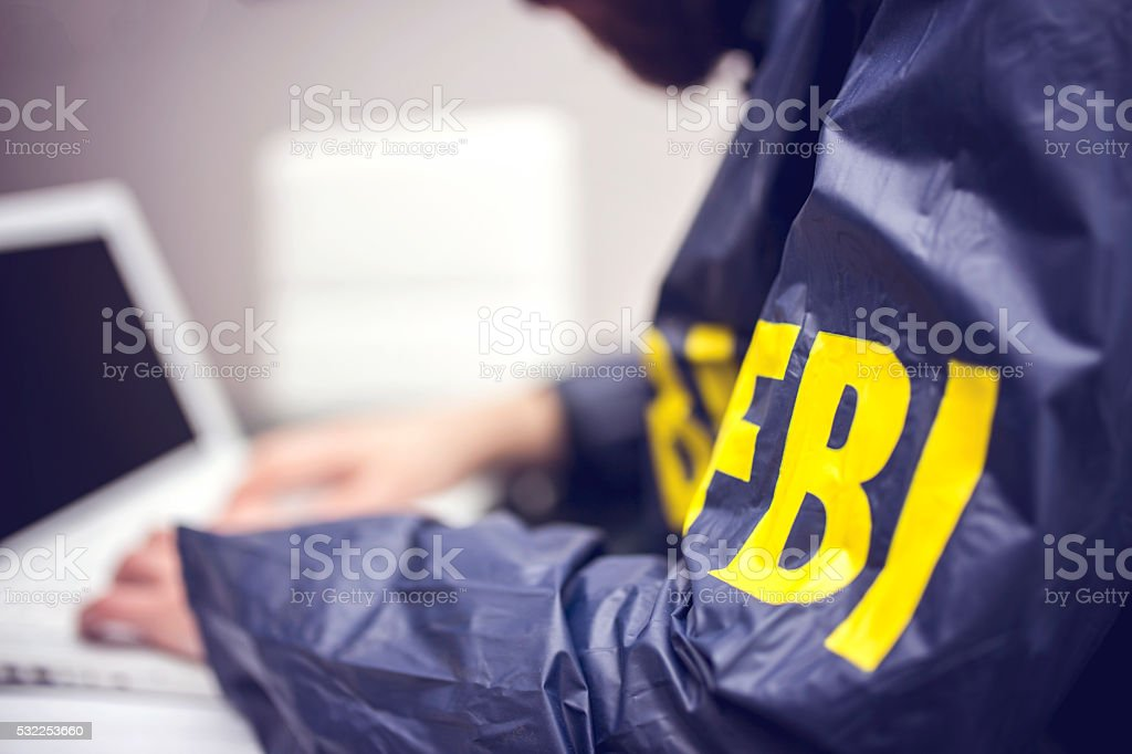 Policeman using laptop in office stock photo