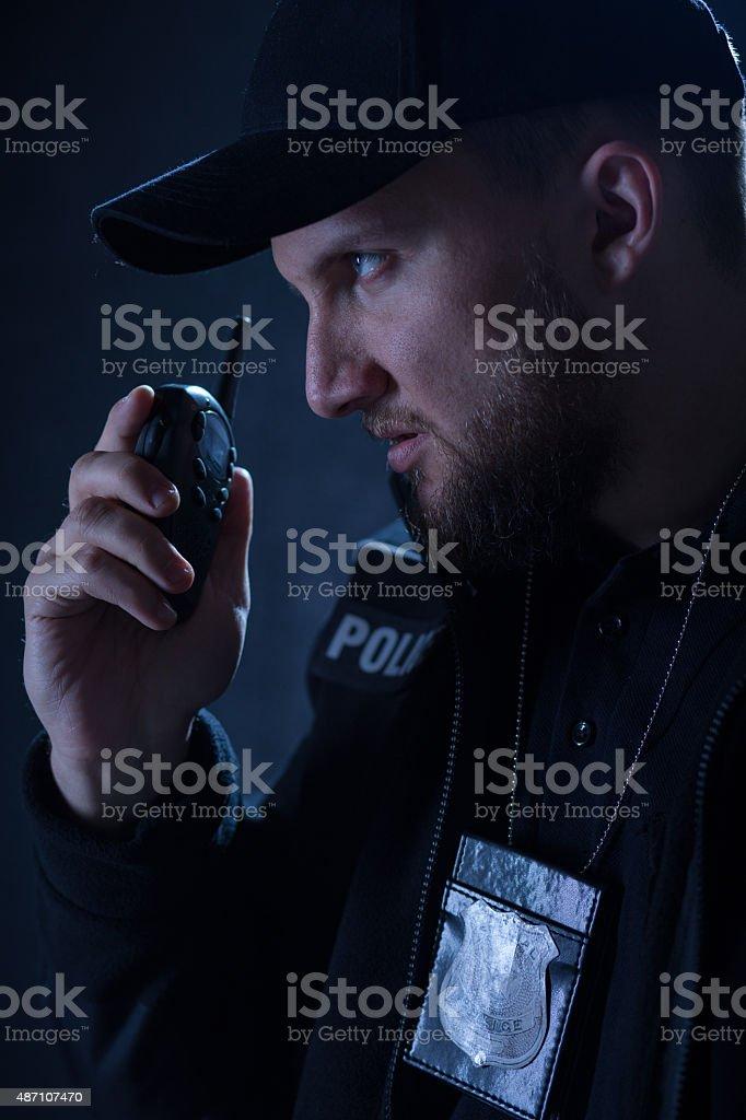 Policeman using walkie talkie stock photo