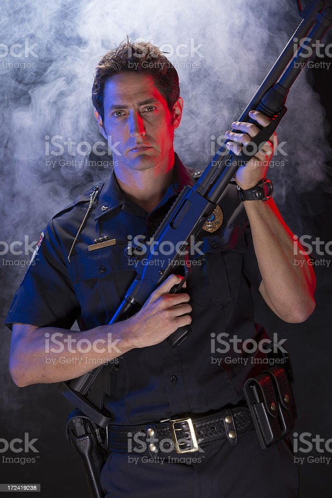 Policeman with a tactical shotgun on smoke background royalty-free stock photo