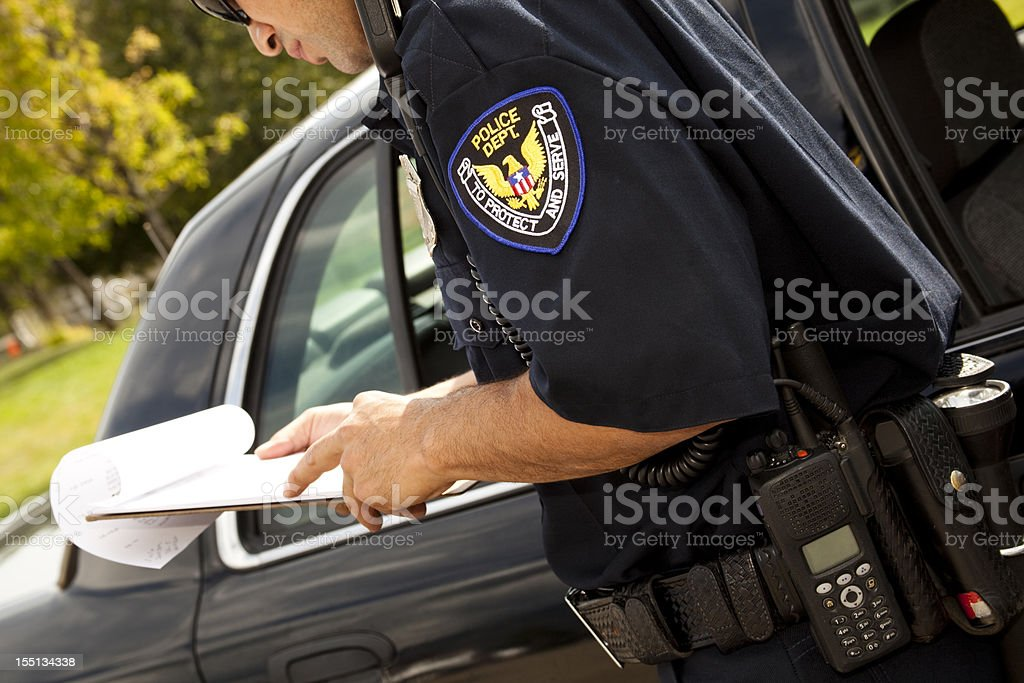 Policeman with clipboard beside police vehicle stock photo