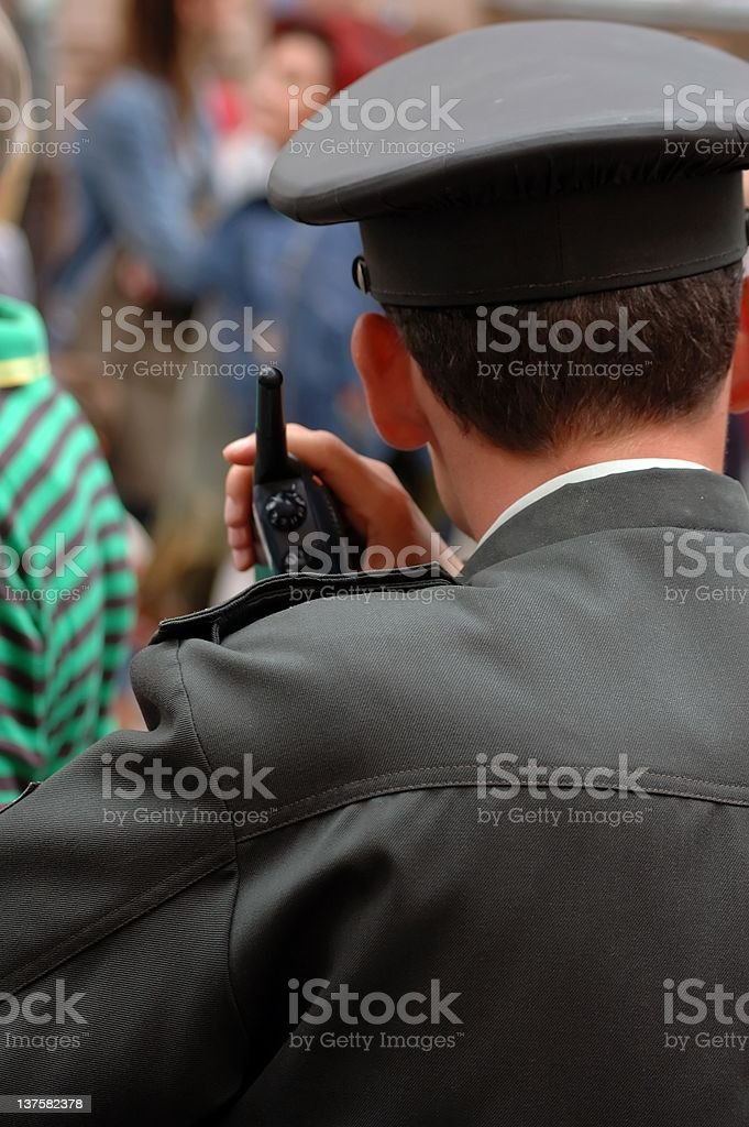 policeman with radio in the crowd royalty-free stock photo