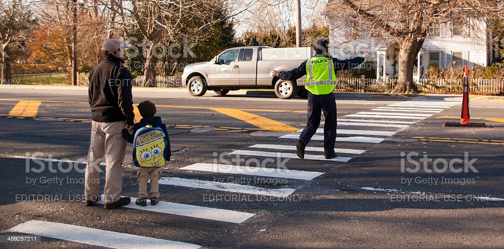 Policewoman assist to phaser and child crossing street stock photo