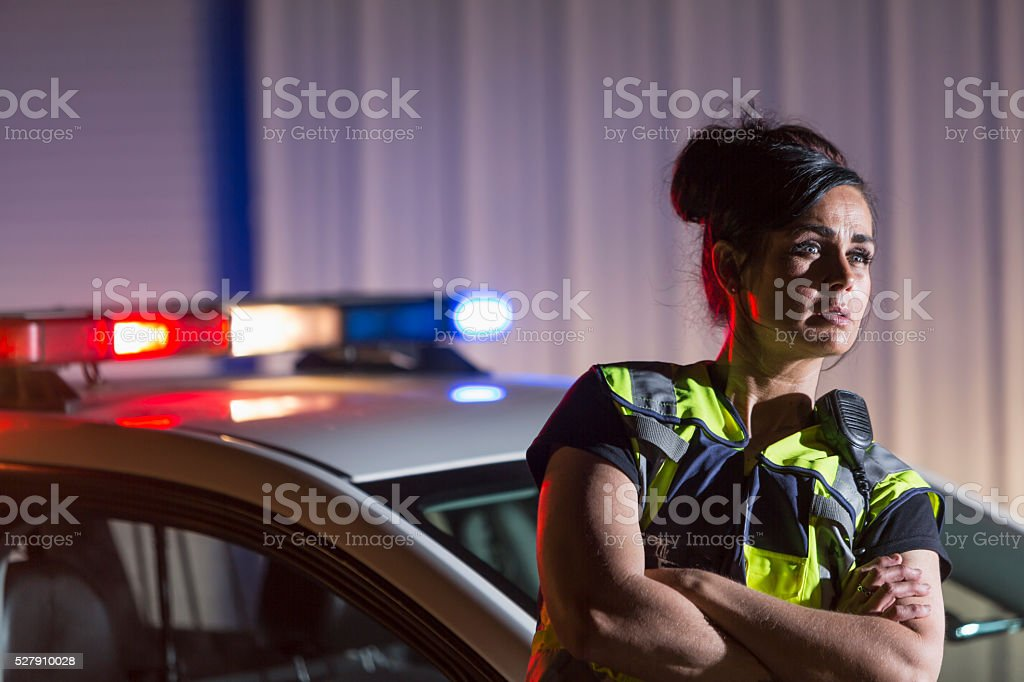 Policewoman at night standing next to police car stock photo
