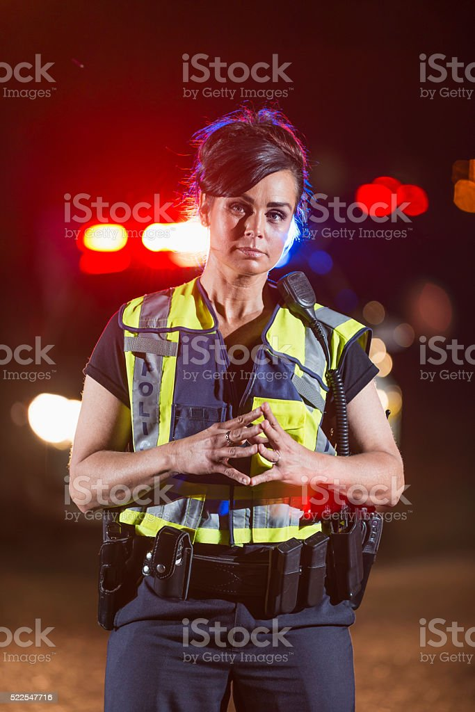 Policewoman in street at night, police car in background stock photo