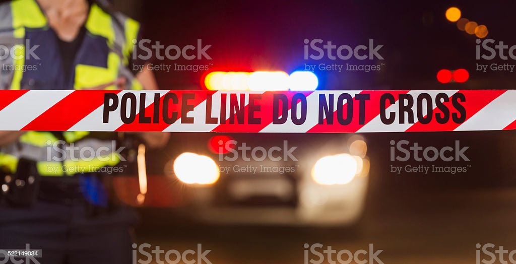 Policewoman standing behind crime scene tape stock photo