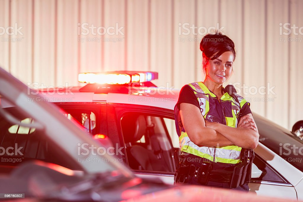 Policewoman standing next to her patrol car, smiling stock photo
