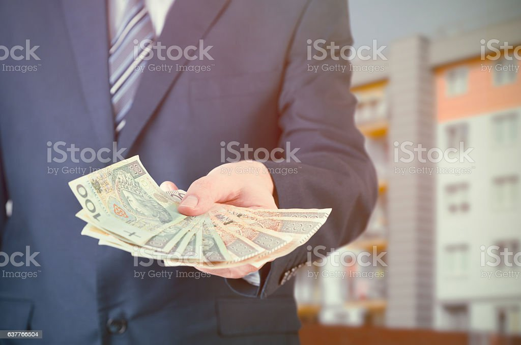 Polish businessman holds money. The loan on the house stock photo