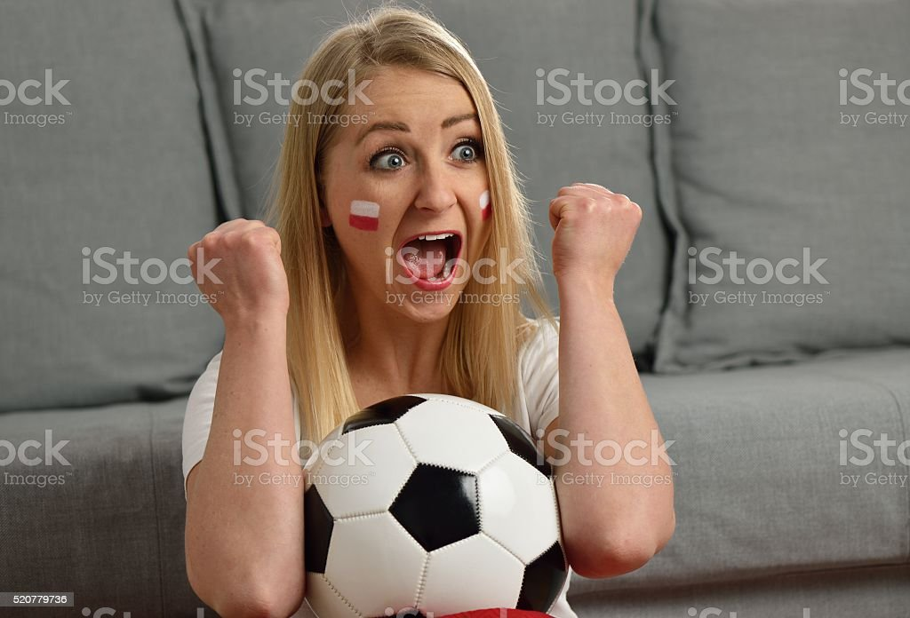 Polish fan cheers football team in the national colors. stock photo