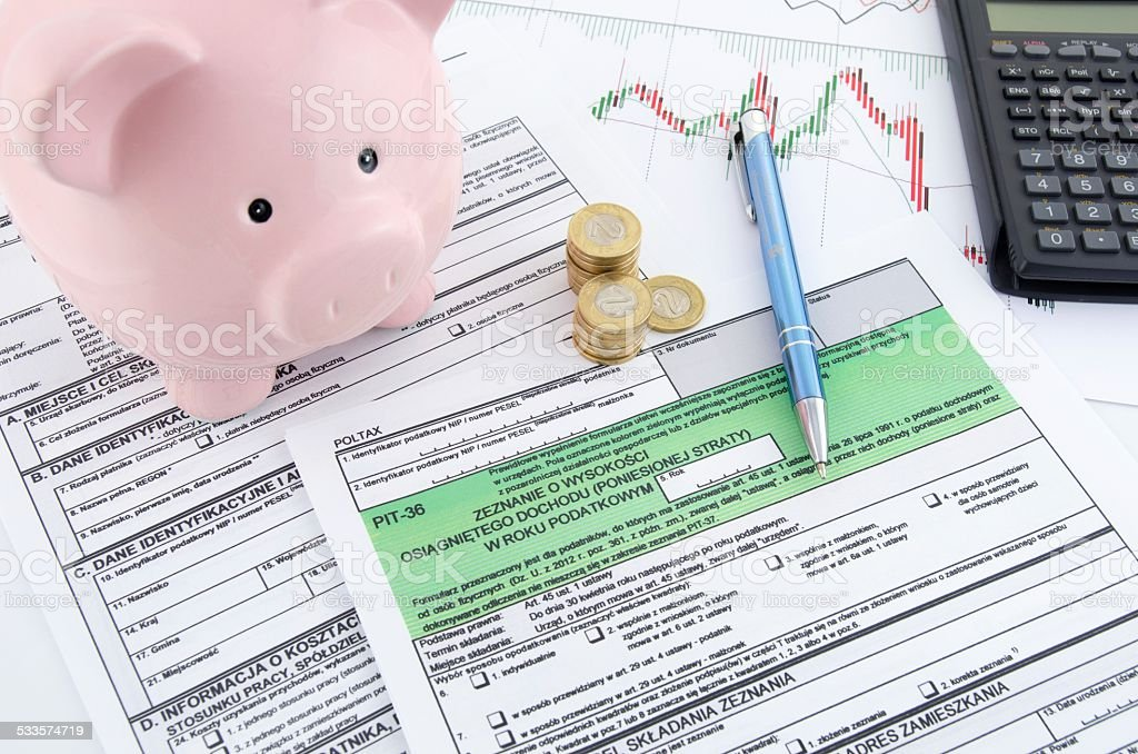 Polish income tax forms with calculator and piggybank stock photo