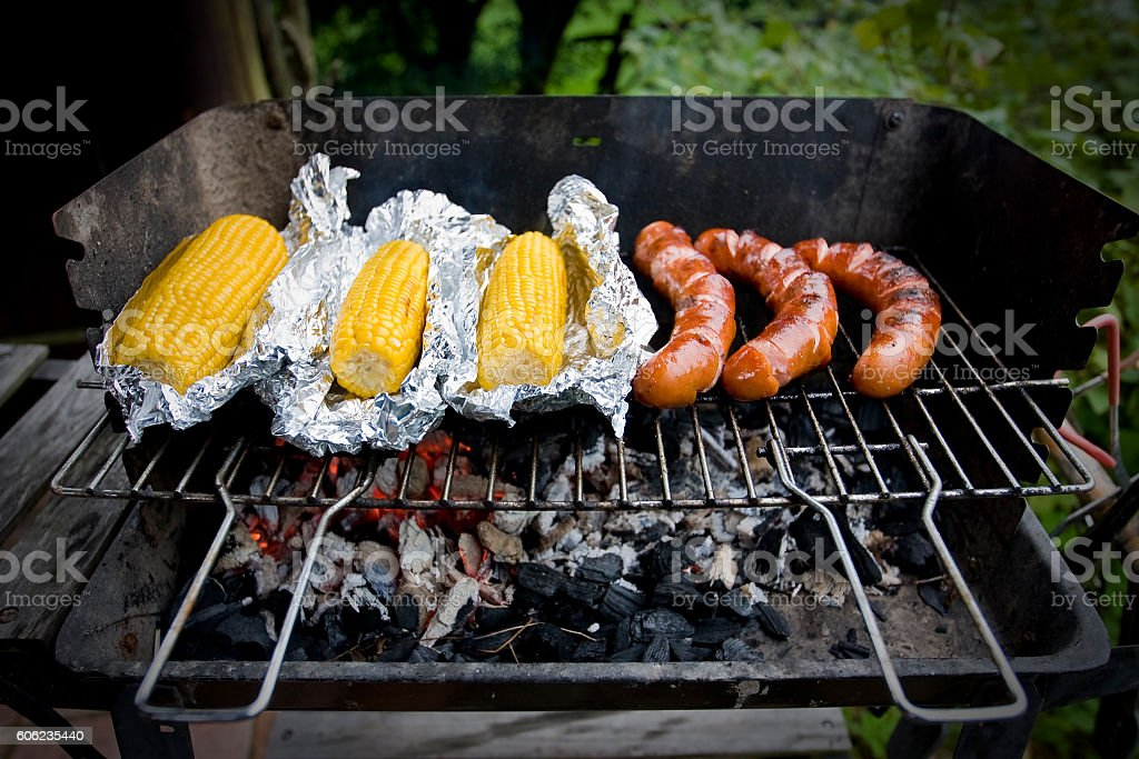 Polish sausage and corn cobs roasted on barbecue stock photo