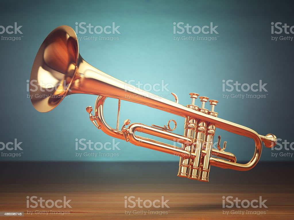 Polished brass trumpet on green background. stock photo
