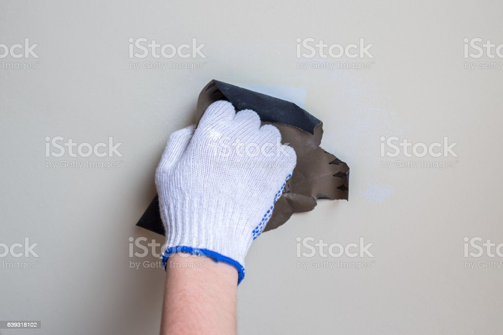polishing a wall with sandpaper closeup stock photo
