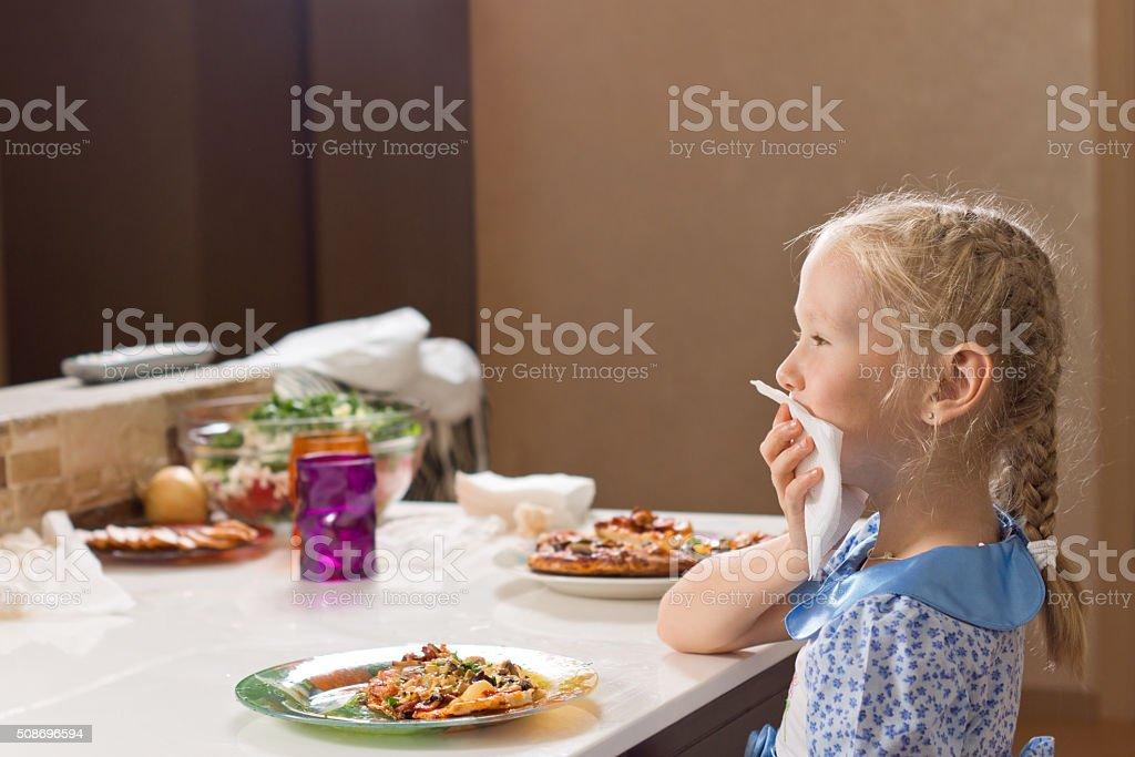 Polite little girl eating homemade pizza stock photo