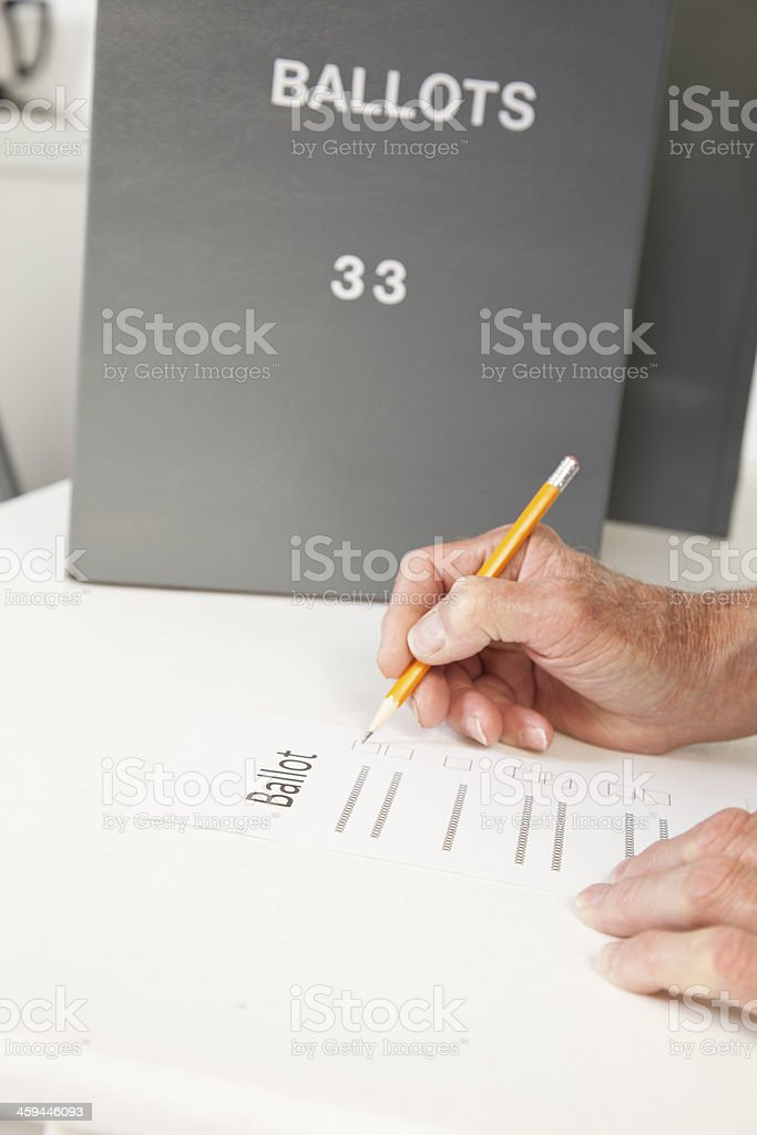 Political Election: Man marks ballot at pollling precinct. royalty-free stock photo